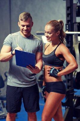 Poster Lächelnde junge Frau mit persönlichen Trainer in der Turnhalle