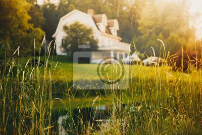 Poster ländliche Ansicht, unscharfer Hintergrund. Teich und Haus in der Ferne bei Sonnenuntergang