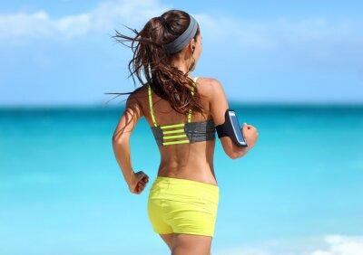 Poster Laufende Motivation - Läufer-Training mit Musik von hinten gesehen Joggen in Mode gelben Riemen Sport-BH und Neon-Shorts-Outfit tragen drahtlose Kopfhörer am Sommer Strand Hintergrund.