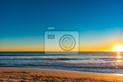 Poster leuchtende gelbe Sonne steigt am Horizont an einem kühlen klaren Morgen am Strand