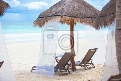 Liegestühle unter strohgedeckten Sonnenschirmen auf tropischen plage