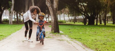 Poster Little boy learning to ride bicycle at park with mother