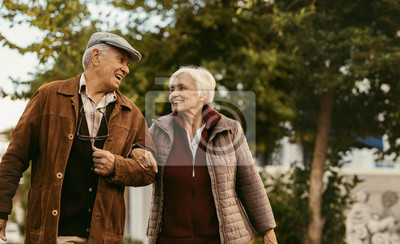 Poster Loving senior couple enjoy a walk together on a winter day