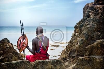 Poster Maasai sitzt am Meer am Strand