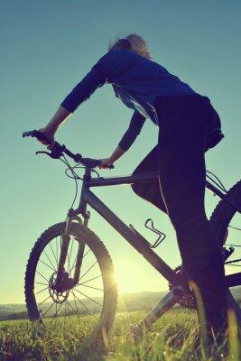 Poster Mädchen auf einem Fahrrad in den Sonnenuntergang