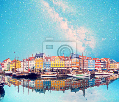 magical fascinating landscape with boats in a famous Nyhavn on the background of the stars and the Milky Way in the capital of Denmark Copenhagen. Exotic amazing places. Popular tourist atraction.