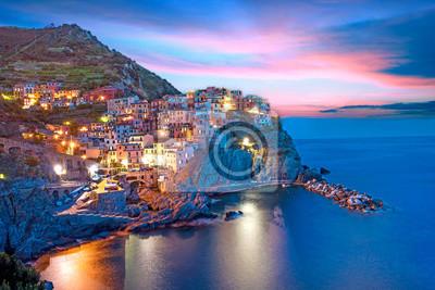 Magische schöne Landschaft mit hellen farbigen Häusern auf dem Felsen auf der Seeküste von Manarola in Cinque Terre, Ligurien, Italien, Europa am Abend