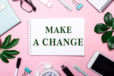 Poster MAKE A CHANGE is written in a white notebook on a pink background surrounded by business accessories and green leaves.