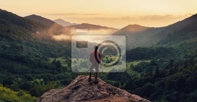Poster Man stand auf der Klippe bei Sonnenuntergang