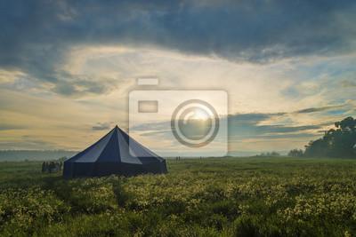 Menschen in der Nähe von Großzelt im nebligen Traumlandschaft