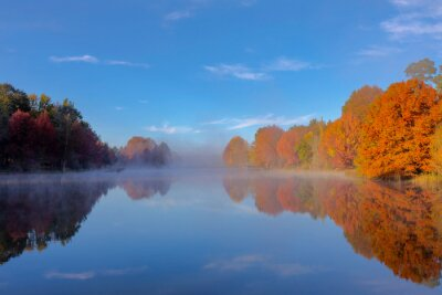 Mist on the water and autumn colored trees