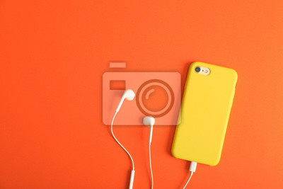 Poster Modern phone with earphones on coral background, top view. Space for text