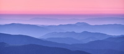 Poster Mountain ridges in fog and pink sky at sunset in autumn. Beautiful landscape with foggy mountain valley, hills, forest at dusk in blue hour in fall. Aerial view of hills. Top view. Nature background