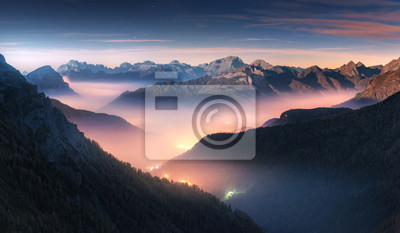 Poster Mountains in fog at beautiful night in autumn in Dolomites, Italy. Landscape with alpine mountain valley, low clouds, forest, colorful sky with stars, city illumination at dusk. Aerial. Passo Giau