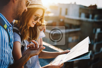 Poster Multiethnic traveler couple using map together on sunny day