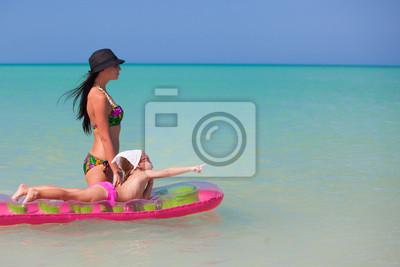 Mutter mit Tochter auf einer Luftmatratze im Meer