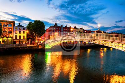 Nachtansicht der berühmten beleuchteten Ha Penny Bridge in Dublin, Irland bei Sonnenuntergang