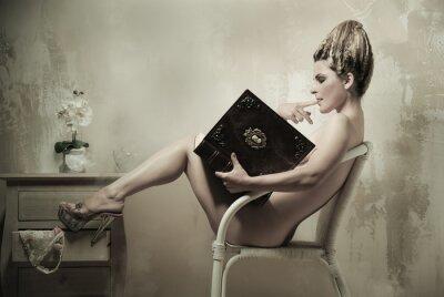 Poster Nackte Frau sitzt auf einem Stuhl ein Buch zu lesen im Innenbereich