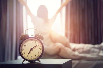 Poster Nahaufnahmewecker, der einen guten Tag mit der glücklichen Frau des Hintergrundes ausdehnt im Bett nachdem dem Aufwachen, Sonnenlicht am Morgen hat.