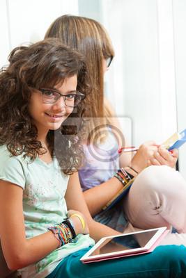 Netter junger Student sitzt mit Tablette.