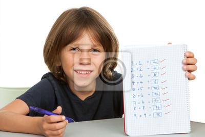Nettes Kind zeigt Notebook mit mathematischen Problemen.