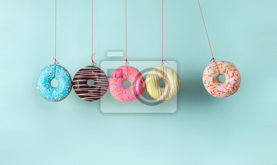 Poster Newton's cradle from doughnuts. Collision balls made from donuts. Harm of sugar, donuts time or healthy diet concept. Dependence on flavoring, diabetes problems, weight loss.