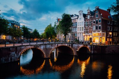 Night city view of Amsterdam canal Herengracht, typical dutch houses in evening dusk lights, Holland, Netherlands