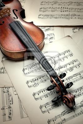Old scratched violin on music sheet. Vintage style.