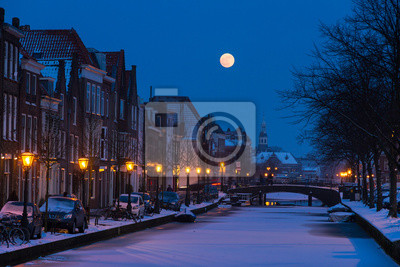 Oude Rijn in Leiden, the Netherlands. A full moon rises over the city canal seen  from a bridge