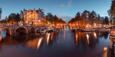Panorama of Amsterdam canal, bridge and typical houses, boats and bicycles during evening twilight blue hour, Holland, Netherlands. Used toning