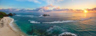 Poster Panoramablick auf tropischen Strand mit Surfern bei Sonnenuntergang.
