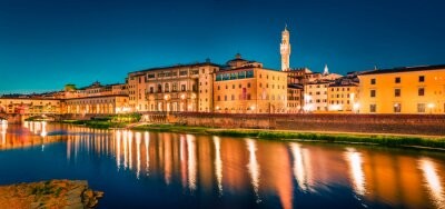 Panoramic evening cityscape of Florence with Old Palace (Palazzo Vecchio or Palazzo della Signoria) on background and Ponte Vecchio bridge over Arno river. Colorful night scene of Italy, Europe.