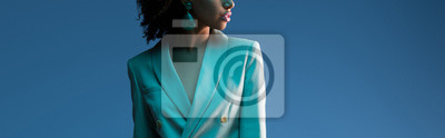 Poster  panoramic shot of african american woman in suit isolated on blue