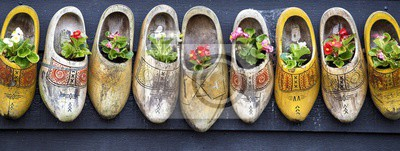 Poster Panoramic shot of beautiful flowers in clog shoes on a gray surface