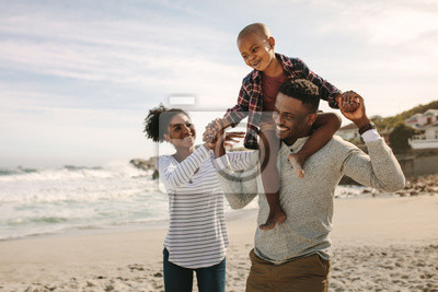 Poster Parents carrying son on shoulders on beach vacation