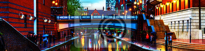 People walking during the rain in the evening at famous Birmingham canal in UK