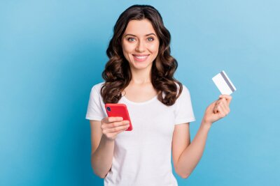 Poster Photo of pretty cute young lady dressed white outfit holding modern gadget bank card isolated blue color background