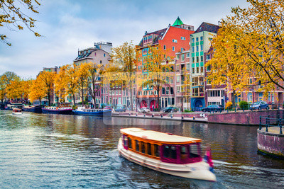 Picturesque autumn cityscape of Amsterdam. Splendid view of famous Dutch channels and excursion boat. Colorful morning landscape in Netherlands, Europe. Traveling concept background.