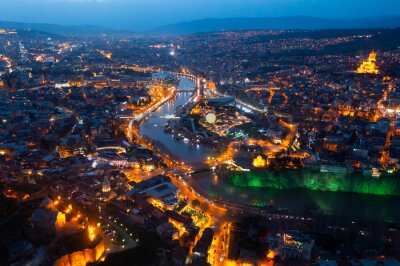 Poster Picturesque general view from drone of Georgian city of Tbilisi on banks of Mtkvari River at spring dusk