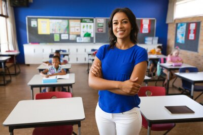 Poster Portrait of african american female teacher with arms crossed smiling in the class at school