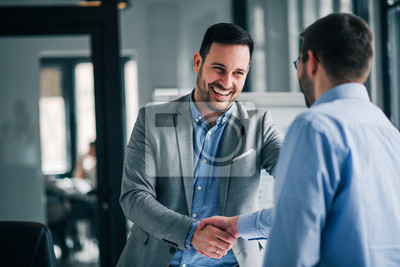 Poster Portrait of cheerful young manager handshake with new employee.