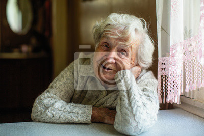 Poster Portrait of elderly pensioner lady sitting at the table.