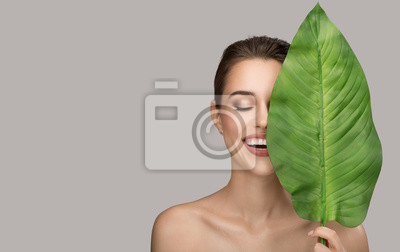 Poster Portrait of woman and green leaf. Organic beauty. Gray background.