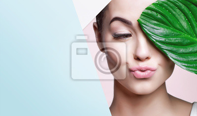 Poster Portrait of young beautiful woman with healthy glow perfect smooth skin holds green tropical leaf, look into the hole of colored paper. Model with natural nude make up. Fashion, beauty, skincare.