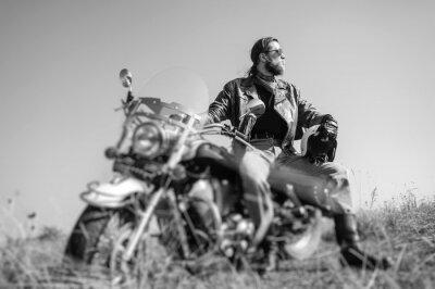 Poster Porträt eines jungen Mannes mit Bart sitzt auf seinem Kreuzer Motorrad und Blick auf die Sonne. Man trägt Lederjacke und Blue Jeans. Niedrige Sicht. Tilt Objektiv Unschärfe-Effekt. Schwarz und weiß