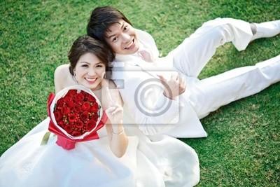 Porträt von Braut und Bräutigam sitzen auf frischem Gras mit Rose bou