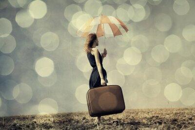Poster Redhead Mädchen mit Regenschirm und Koffer bei windigen Feld