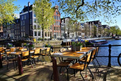 Poster Restaurant tables lining the beautiful canals of Amsterdam under blue skies during springtime, Netherlands