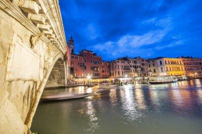 Rialto Bridge at night with city restaurants along grand canal, Venice, Italy
