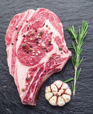 Poster Rib Auge Steak mit Gewürzen auf dem schwarzen Hintergrund.